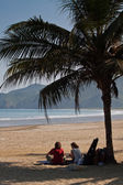 Unidentified tourists relaxing under a palm tree in peaceful beach, Manabi, Ecuador — Stock Photo