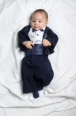 Cute baby boy wearing an elegant suit with bow tie — Stock Photo