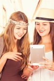 Beautiful young trendy girls using tablet — Stock Photo
