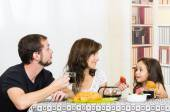 Young sweet parents with one little girl having breakfast — Stock Photo