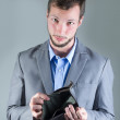 Portrait of young handsome man holding empty wallet — Stock Photo #73457853