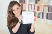 Portrait of pretty brunette girl holding up a calendar — Stock Photo