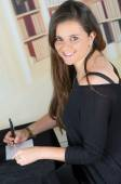 Brunette girl sitting and writing on a paper — Stockfoto