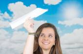 Brunette holding a paperplane in front of cloud themed background — Stock Photo