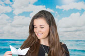 Brunette holding an origami paper figure in front of oceanic cloud background — 图库照片