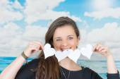 Brunette holding an origami paper figure in front of oceanic cloud background — Stock Photo