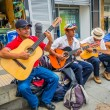 Постер, плакат: Unidentify indigenous men playing guitar in the commercial street plaza of Armenia Colombia