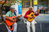 Two unidentify indigenous men playing guitar in the commercial street of Armenia, Colombia — 图库照片