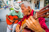 Two unidentify indigenous men playing guitar in the commercial street of Armenia, Colombia — Stock Photo