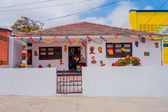 One storey white house with roof tiles and Carnival colorful elaborate decorations during Colombias most important folklore celebration the festivities of Barranquilla — Stock Photo