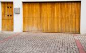 Wooden light colored entrance and garage door with stone tiles in front — Stock Photo