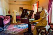 Living room decorated in wooden tables including gold painted details, yellow carpet with a female dress sitting by piano and another attire across simulating daily life at residence Bogota Colombia — Stock Photo