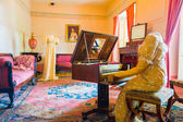 Living room decorated in wooden tables including gold painted details, yellow carpet with a female dress sitting by piano and another woman across simulating daily life at residence Bogota Colombia — Stock Photo