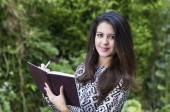 Hispanic brunette business woman in park environment wearing formal clothing taking notes and looking to camera carefully smiling — Stock Photo