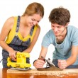 Couple standing by working desk as woman uses electric sander and man holding a manual version — Stock Photo #78118262