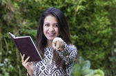 Hispanic brunette business woman in park environment wearing formal clothing holding book open while pointing into camera and smiling — Stock Photo