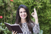 Hispanic brunette business woman in park environment wearing formal clothing holding book open while making circle using left thumb and point finger as expressing positive vibes plus smiling happily — Stock Photo