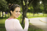 Hispanic brunette model in park wearing white top caption of upper body sideways angle smiling to camera — Stock Photo