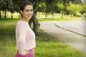 Hispanic brunette wearing yoga clothing in park environment standing on grass looking to camera from sideways profile angle — Stock Photo