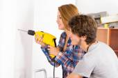 Couple renovating together as woman using power drill on wall with man standing next to her observing — Stock Photo