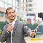 Man wearing formal clothing posing with selfie stick in urban environment smiling making gun of right hand — Stock Photo #78160694