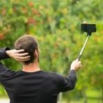 Hispanic man posing with selfie stick in park environment, his back facing camera — Stock Photo #78161092