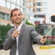 Man wearing formal clothing posing with selfie stick in urban environment smiling making gun of right hand plus red bus background. — Stock Photo #78161102