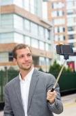 Man formal clothing posing with selfie stick in urban environment — Stock Photo