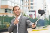 Man wearing formal clothing posing with selfie stick in urban environment smiling making gun of right hand — Stock Photo