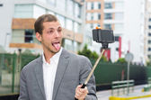 Man formal clothing posing with selfie stick in urban environment showing tongue — Stock Photo