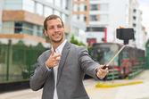 Man wearing formal clothing posing with selfie stick in urban environment smiling making gun of right hand plus red bus background. — Stock Photo