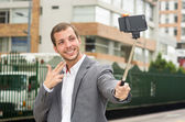 Man wearing formal clothing posing with selfie stick in urban environment smiling using right hand to make a signal — Stock Photo