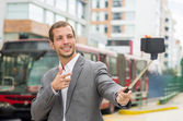 Man wearing formal clothing posing with selfie stick in urban environment smiling making gun of right hand plus red bus background — Stock Photo