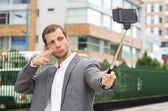 Man wearing formal clothing posing with selfie stick in urban environment using right hand to make a signal — Stock Photo