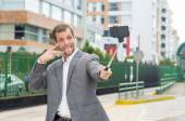 Man wearing formal clothing posing with selfie stick in urban environment smiling using right hand to make a signal while tongue is out — Stock Photo