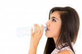 Beautiful young girl drinking water from a plastic bottle — Stock Photo
