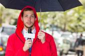 Successful handsome male journalist wearing red rain jacket working in rainy weather outdoors park environment holding microphone and umbrella, live broadcasting — Stock Photo