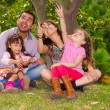 Family portrait of father, mother and two daughters sitting together in garden environment pointing looking upwards towards the sky — Stockfoto #79577216