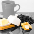 Grey coffe cup on shiny surface sourrounded by cheese, small toasts and coffee beans — Stock Photo #79808310