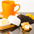 Strong yellow coffe cup on shiny surface sourrounded by cheese, small toasts and coffee beans — Stock Photo #79976436