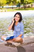 Brunette model wearing denim shirt and white shorts relaxing in park environment, sitting on bench next to lake using phone — Stock Photo