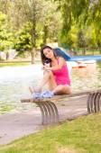身穿粉红色上衣和白色短裤放松在公园的环境中,使用驱蚊喷雾的湖旁边的长椅上坐着的黑发模型 — 图库照片