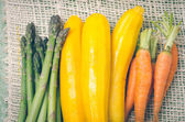 Bunch of brightly colored fresh asparagus, zucchinis and carrots in piles next to each other on a hemp cloth — Stock Photo