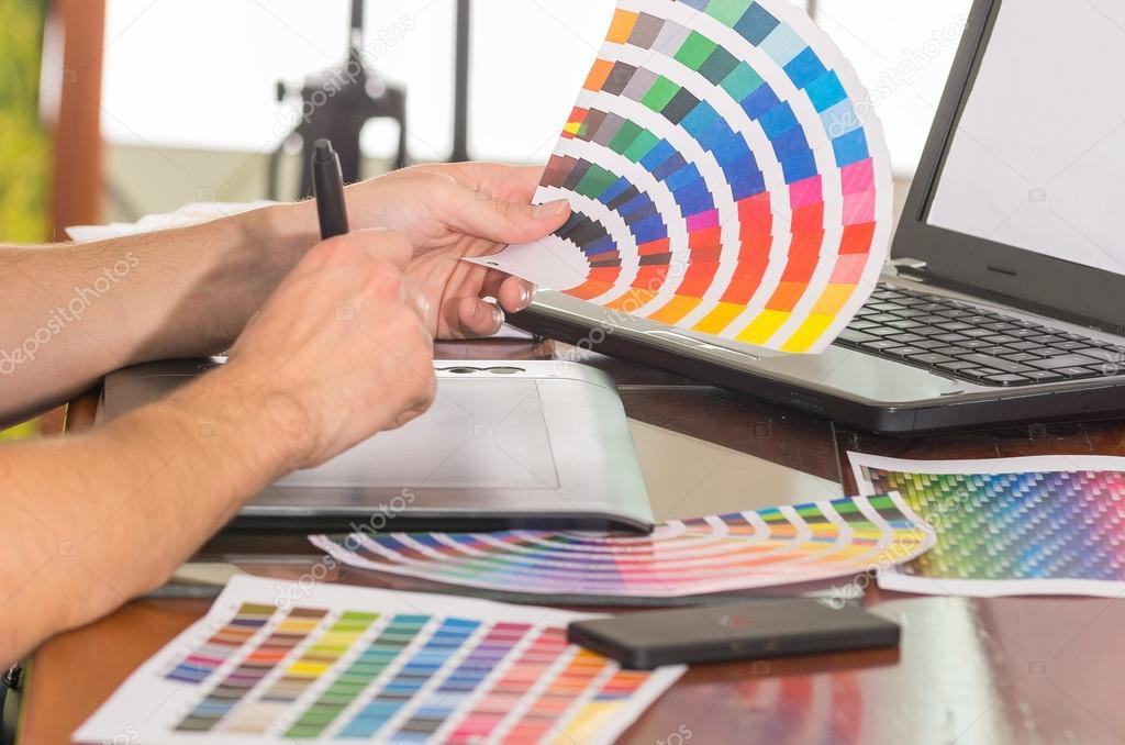 남성 손 pantone 팔레트를 들고, 색상표 작업 책상에 노트북 앞에서 ...