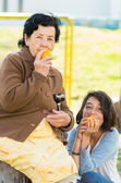 Grandmother granddaughter quality time outdoors holding an orange — Stock Photo