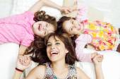 Young adorable hispanic sisters with mother lying down, heads touching and bodies spread out different directions closeup — Stock Photo