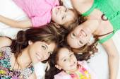 Young adorable hispanic girls and mothers lying down with heads touching, bodies spread out different directions closeup — Stock Photo