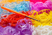 Colorful rubber bands and a hook tool — Stock Photo