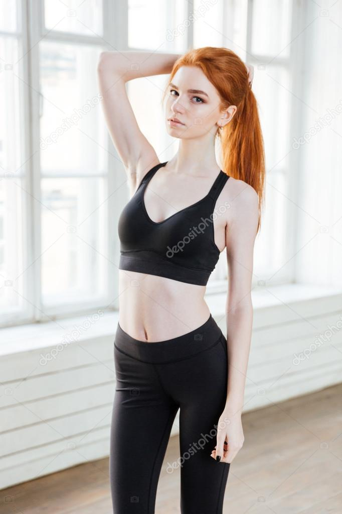 Attractive girl with red hair wearing sport uniform at gym ...