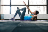 Young woman lying on the yoga mat and doing exercise — Stock Photo